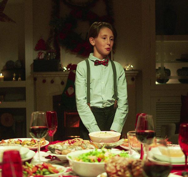 Niño delante de la mesa de cena de Navidad